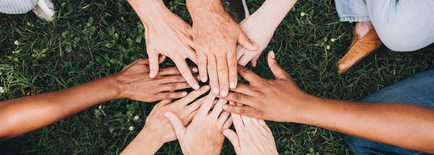 A group of hands reaching into the center of a circle and touching; group psychotherapy in Parker