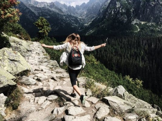 A girl hiking in the mountains with her arms spread in enjoyment after individual counseling in Parker