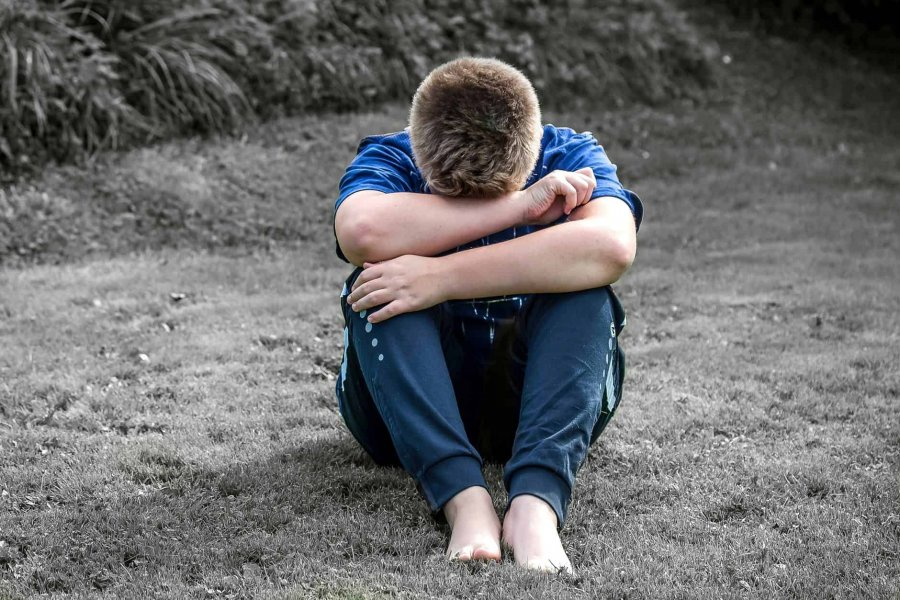 An adolescent boy sitting with his head down on his arms perhaps needing depression therapy